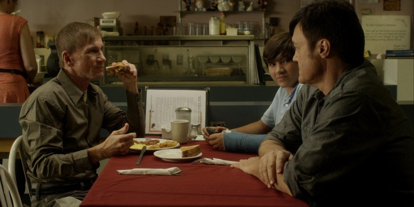 Denis (Bill Oberst Jr.) heightens Gordon's sense of unease as Gordon's son Paul (Mateo D'Avino) looks on.