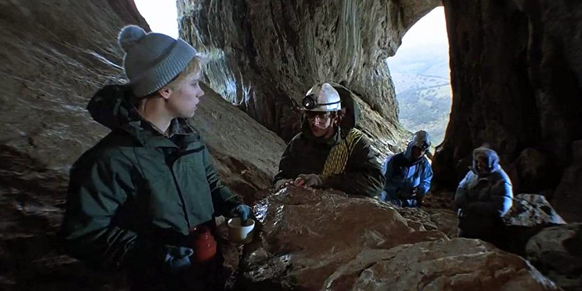 Four people explore a large stone cavern