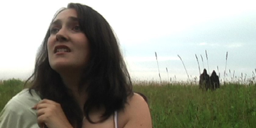 A woman in a field with two hooded figures in the background