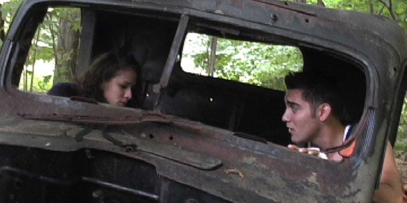 Couple sitting in a rusted out truck