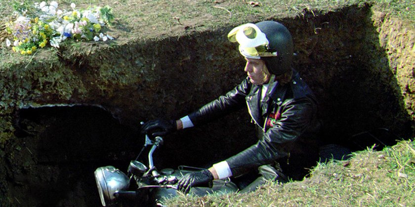 Corpse sitting on motorcycle in a grave