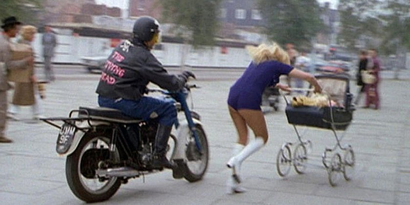 Man on a motorcycle chasing a woman pushing a baby carriage