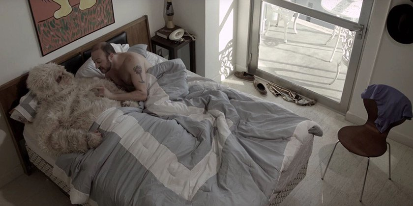 A man and a yeti have a romantic moment in bed